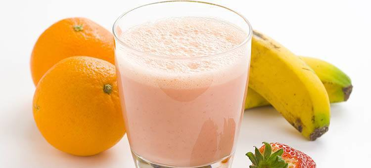 A glass of banana strawberry smoothie next to some oranges and bananas.