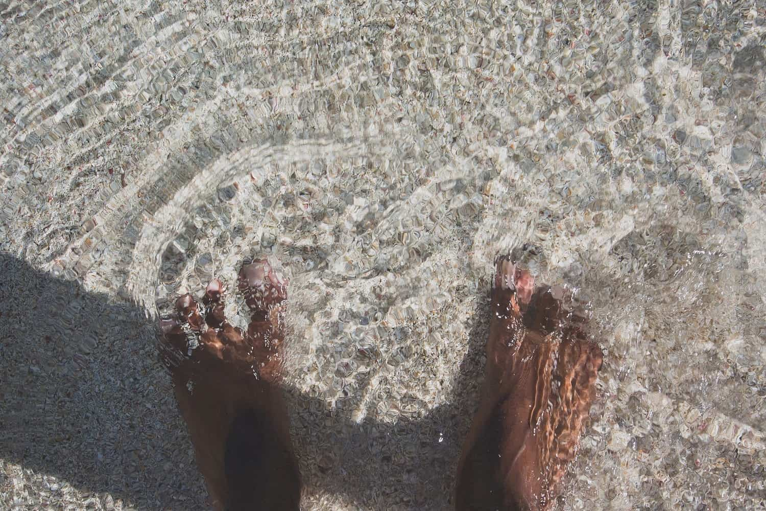 A man's feet in water on a sandy beach.