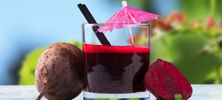 Beet juice in a glass next to beetroot.