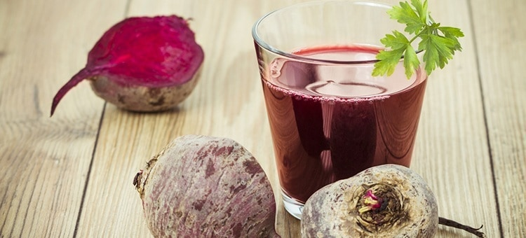 A glass of beet juice next to beetroots.