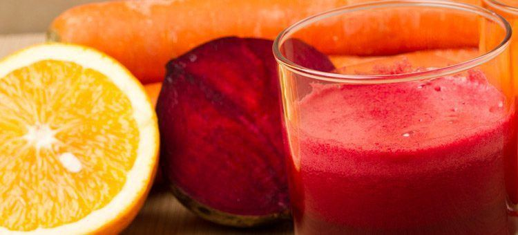 A glass of beet juice with an orange and a carrot.