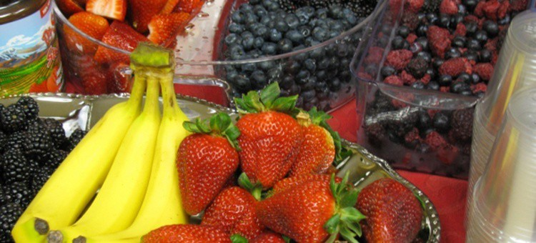 Various berries in bowls with some bananas.
