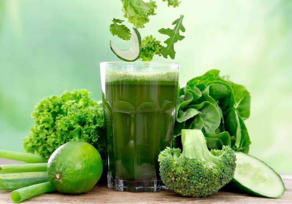 A glass of green vegetable juice surrounded by greens like broccoli, cucumber, salad, kale, and lime.