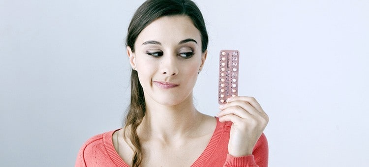 A young woman looking at birth control pills with suspicion.