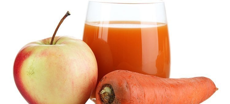 A glass of carrot apple juice next to an apple and carrot.