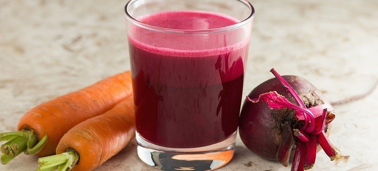A glass of carrot beet juice next to a beetroot and carrots.