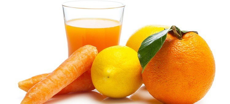 A glass of carrot-orange juice surrounded by lemons, a carrot, and an orange.