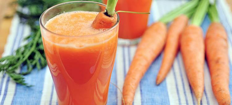 Carrot smoothie in a glass with a few carrots next to it.