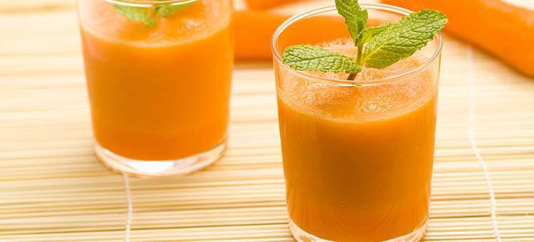 Glasses of carrot smoothie with mint leaves as decoration.