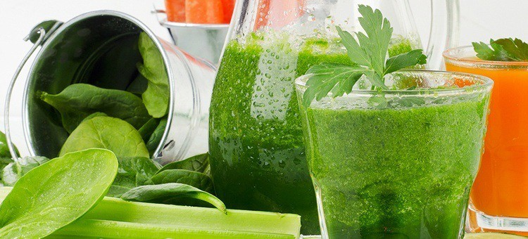 A glass of carrot-spinach-celery juice next to celery.