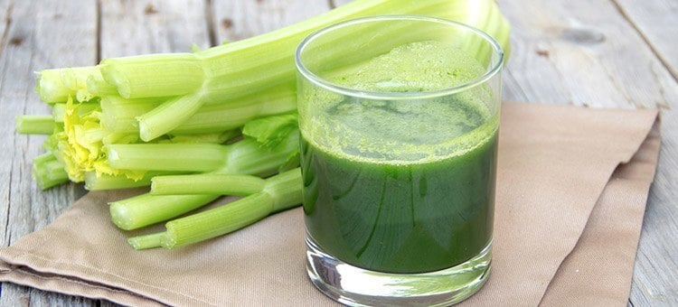 A glass of celery juice next to some celery.
