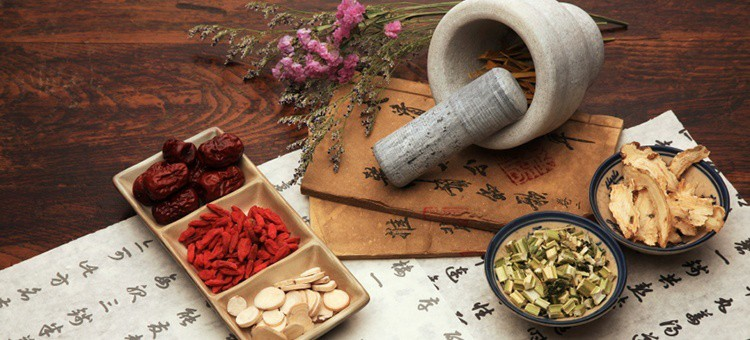 Various Chinese herbs surrounded by tablets with Chinese symbols.