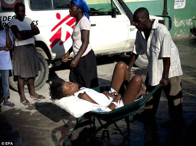 Person escorting his partner to a hospital using a wheelbarrow in Haiti.