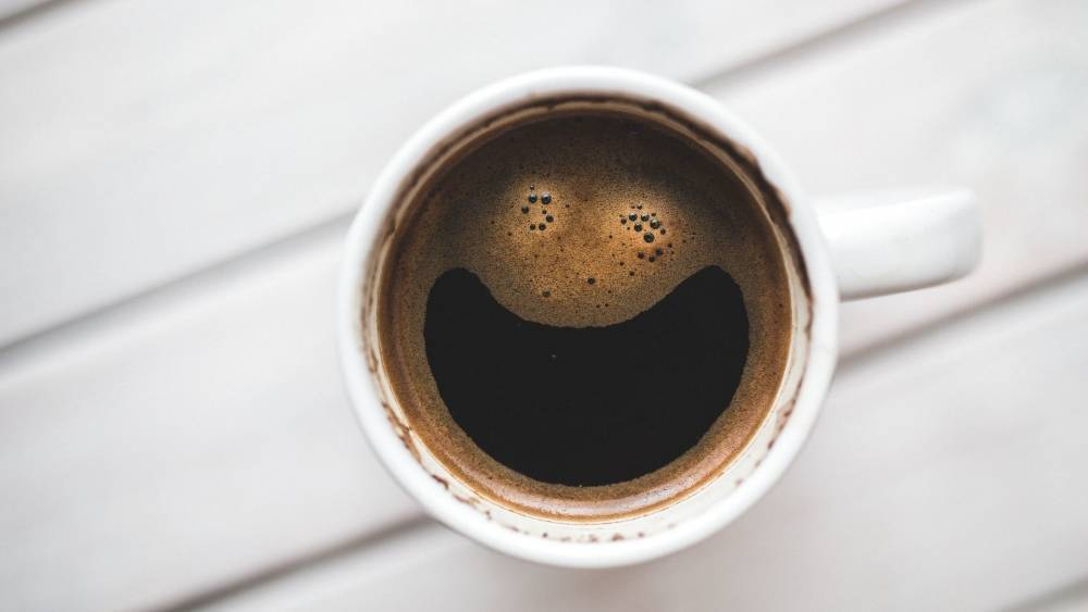A cup of coffee with a smiley-shaped foam.