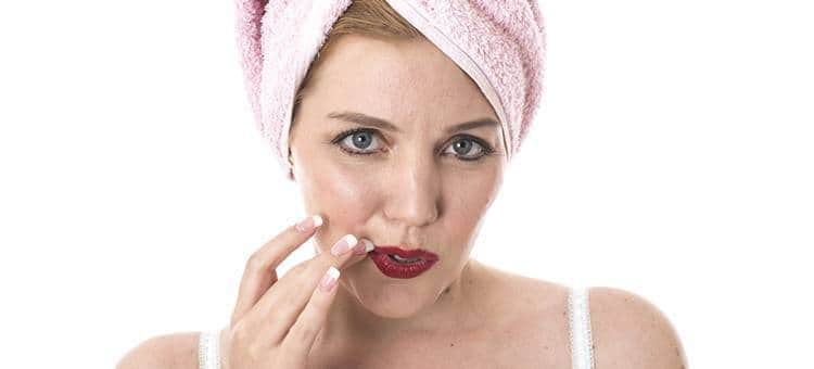A woman with a towel on her head touching her lip with her finger.