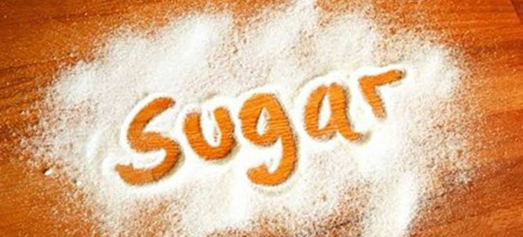 The word SUGAR written in a pile of sugar.