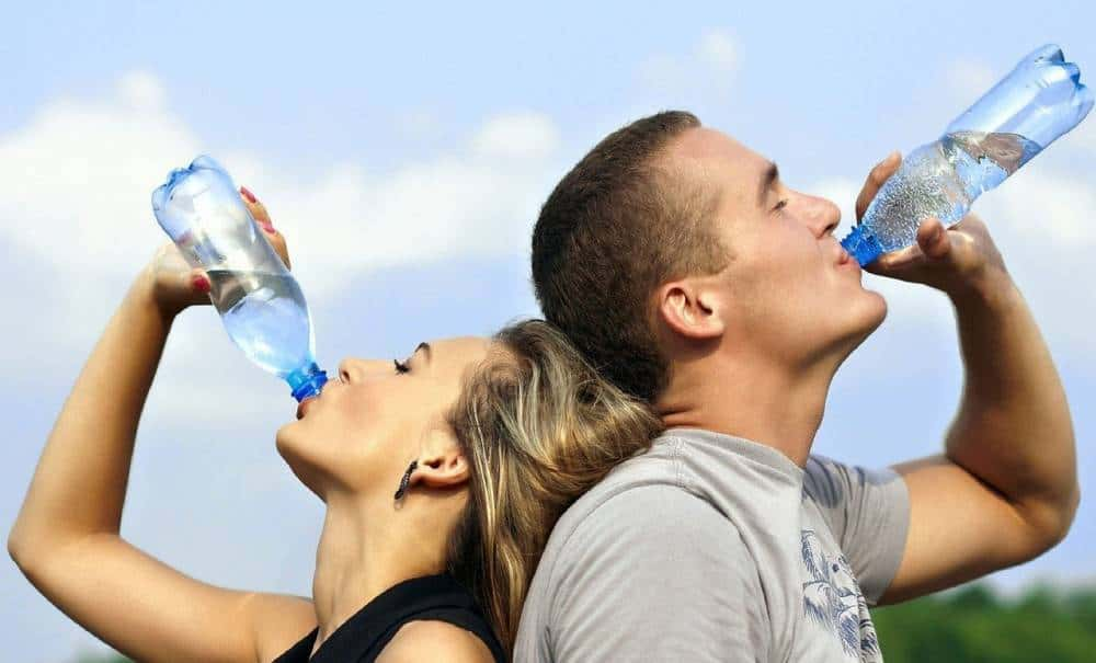 A couple drinking water during exercise.