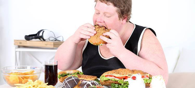 An obese man eating a burger.