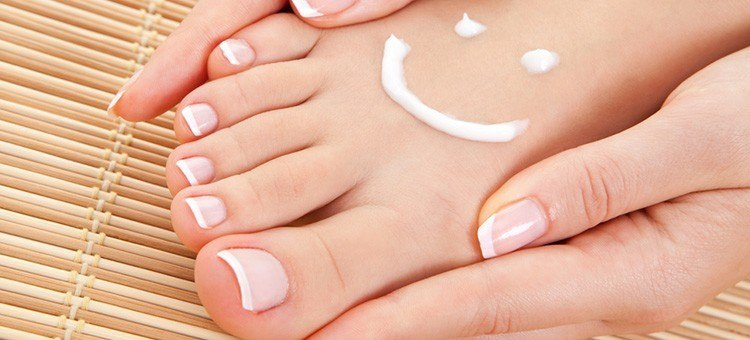 A woman holding her foot which has a smiley face drawn on it with body lotion.
