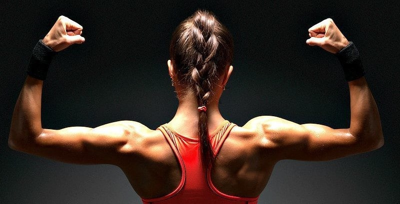 A woman flexing her shoulders.