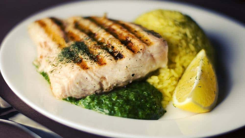 Chicken breast on a plate with spinach and mustard.