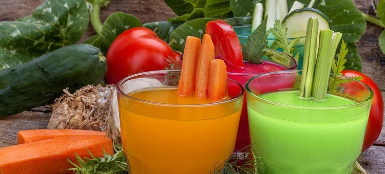 Three glasses of orange, red and green colored juices with various vegetables around them.