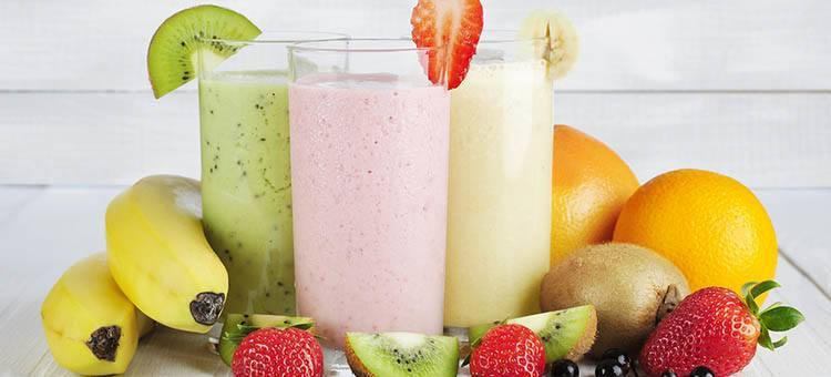 Glasses of various smoothies surrounded by fruit.