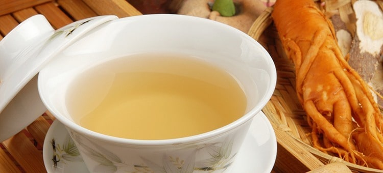 A cup of ginseng tea next to a ginseng root.