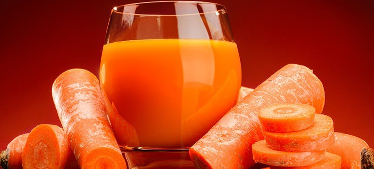 A glass of carrot juice next to some carrots.