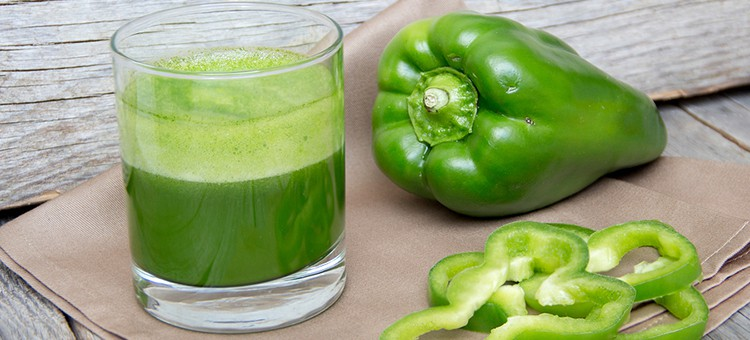 A glass of green juice with pepper slices and a whole pepper next to it.