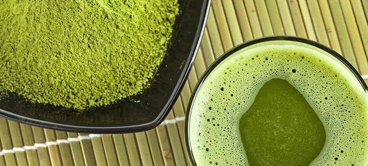 A cup of matcha tea next to a small plate of matcha powder.