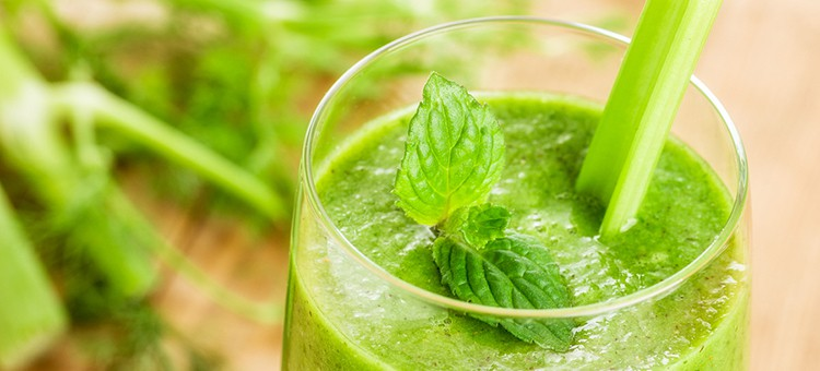 A glass of green celery smoothie with mint on top.