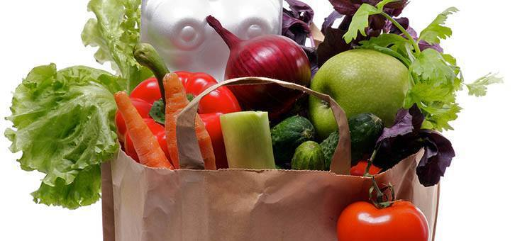 A bag of groceries including vegetables and fruit.