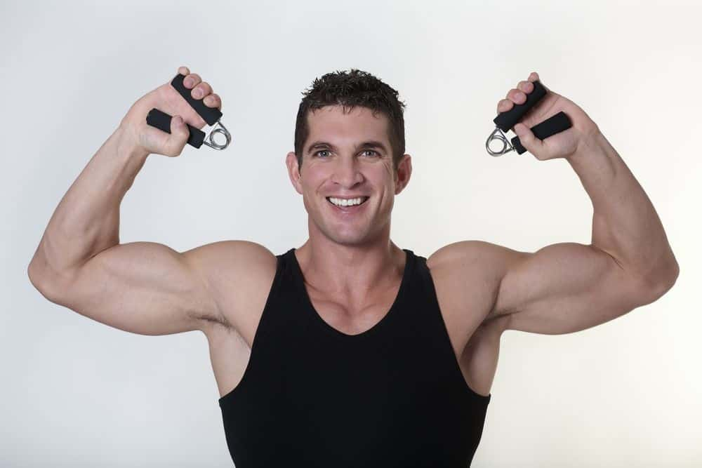 A muscular man gleefully using hand-grippers to exercise.