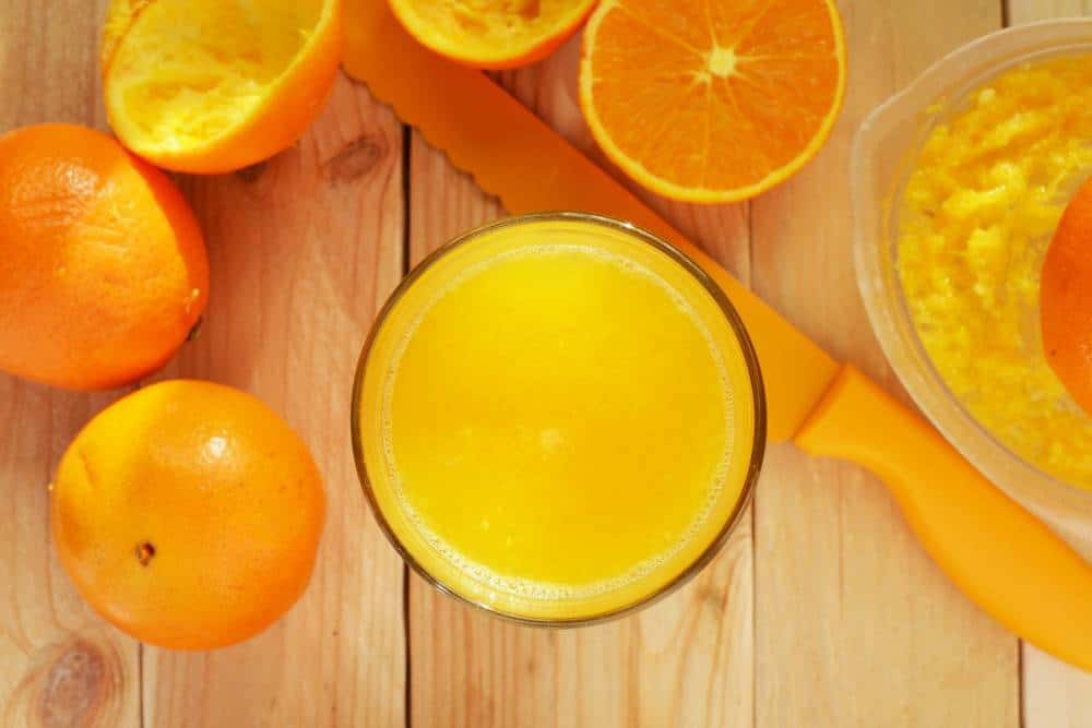 Orange juice with oranges around it.