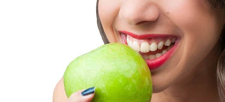 A woman with very healthy gums and teeth, biting into a fresh apple.