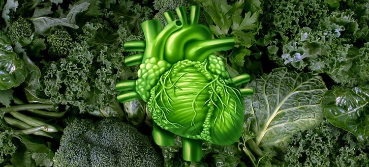 A humna heart made up of green fibers in front of a background of vegetables.