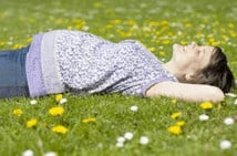 A woman sleeping on her back in the grass.
