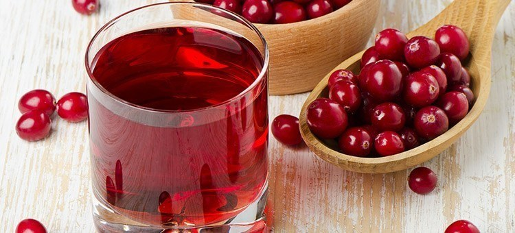 A glass of cranberry juice with a spoonful of cranberries.
