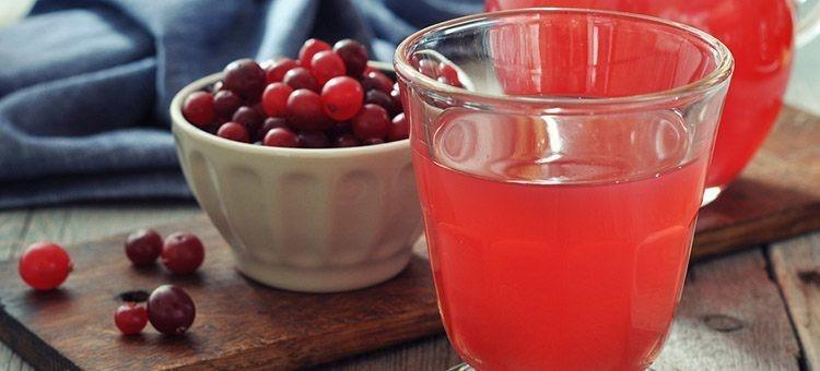 A glass of cranberry juice with a cup of cranberries.