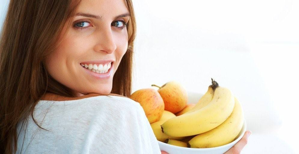 A woman smiling next to some fruit.