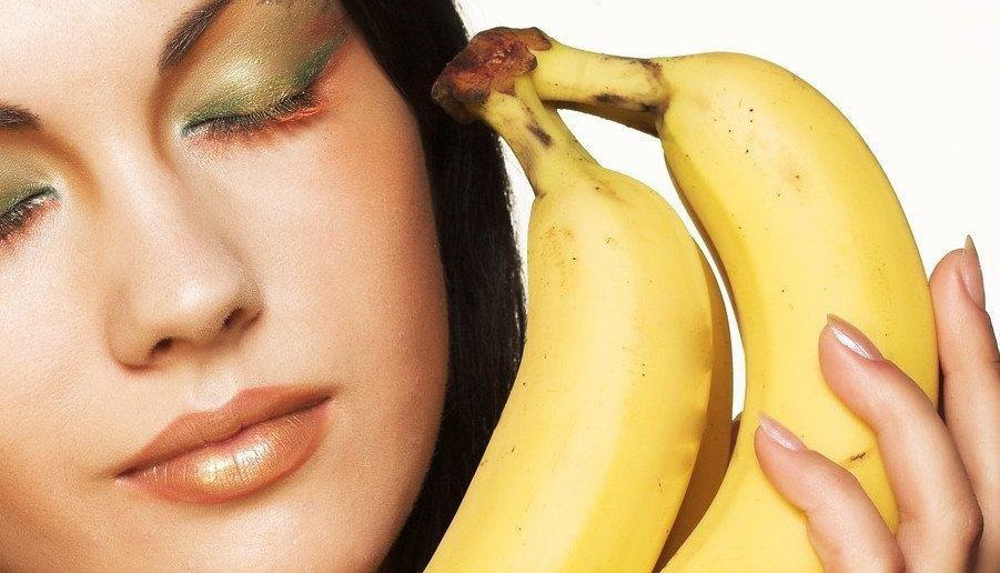 A model holding bananas next to her face.