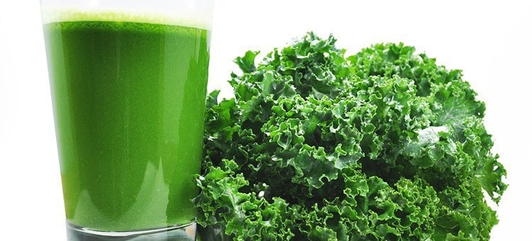 A glass of kale juice next to kale.