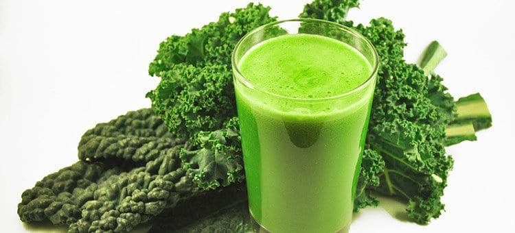 A glass of kale juice next to some kale.