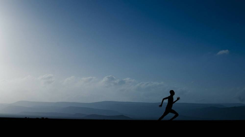 A person running in front of a landscape