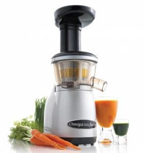 A juicer machine with two glasse sof juice and vegetables next to it.