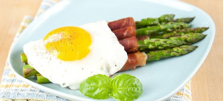 A plate of egg, bacon and vegetable breakfast.