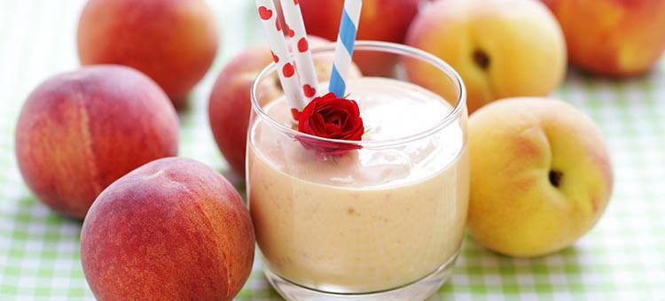 A glass of peach smoothie next to some peaches.