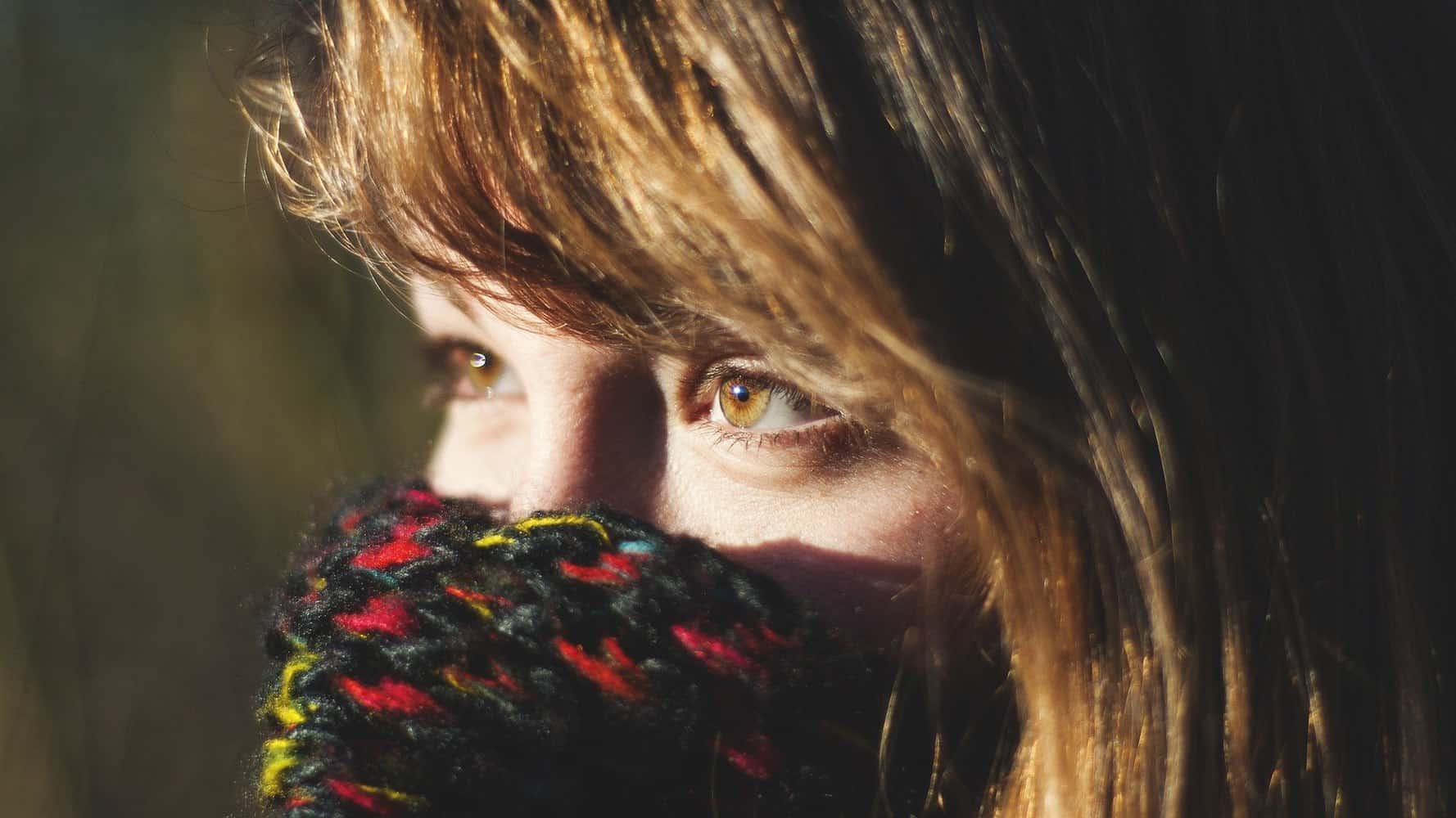A girl wearing a scarf that covers her nose.
