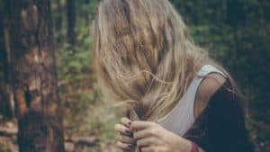 A girl fiddling with split hairs in a forest.